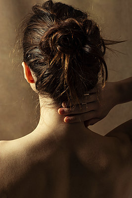 Rear view of topless woman hand touching neck  - p794m2159017 by Mohamad Itani