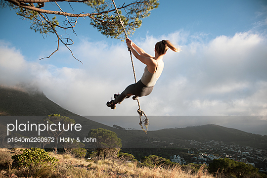 Blond woman swings on a rope in the mountains - p1640m2260972 by Holly & John