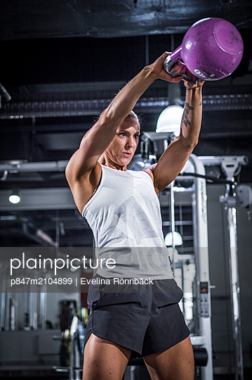 An Athletic Woman Exercising With Kettlebell In Gym   - p847m2104899 by Evelina Rönnbäck