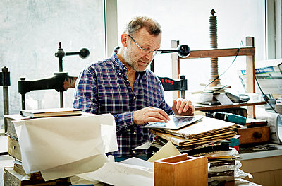 A man using a digital tablet in a bookbinding workshop. - p1100m1158350 by Mint Images