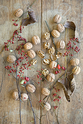 Whole and cracked organic walnuts, leaves and roseships on wood - p300m2069108 by Achim Sass