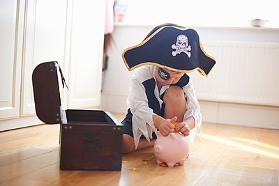 Young boy dressed as pirate, putting money into piggy bank - p429m1504637 by Peter Muller