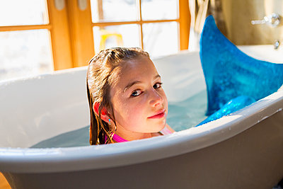 Caucasian girl wearing mermaid tail in bath - p555m1412743 by Marc Romanelli