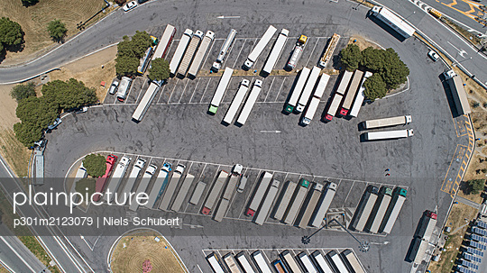 Aerial view from above semi-trucks parked in sunny rest stop parking lot - p301m2123079 by Niels Schubert