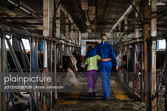 Woman with daughter in cowshed - p312m2080109 by Anna Johnsson