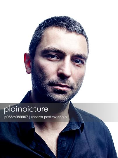 Mid adult man portrait on black - p968m989967 by Roberto Pastrovicchio
