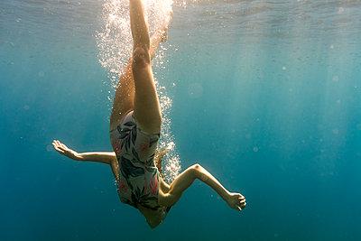Woman swimming upside down in sea - p1166m1174119 by Cavan Images