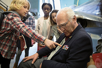 Curious boy student asking war veteran about stripes in war museum - p1192m1447271 by Hero Images