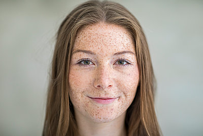 Portrait of young woman with freckles - p276m2111134 by plainpicture