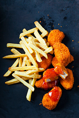 Chicken Nuggets with sweet chili sauce and French Fries on dark ground - p300m1567766 by Dieter Heinemann