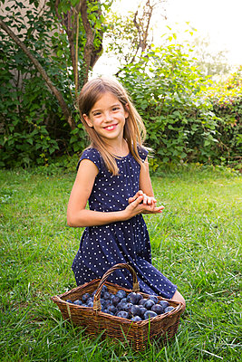 Portrait of smiling girl on a meadow with wickerbasket of plums - p300m2081098 by Larissa Veronesi