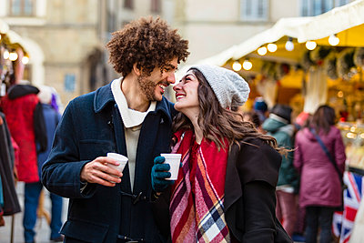 Happy affectionate young couple with hot drinks at Christmas market - p300m2083779 by Giorgio Magini