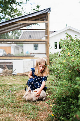 Girl playing with rabbit - p312m2091619 by Anna Johnsson