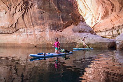 Two women paddleboarding through Cathedral in the Desert, Glen Canyon, Lake Powell, Utah, USA - p343m1578138 by Suzanne Stroeer