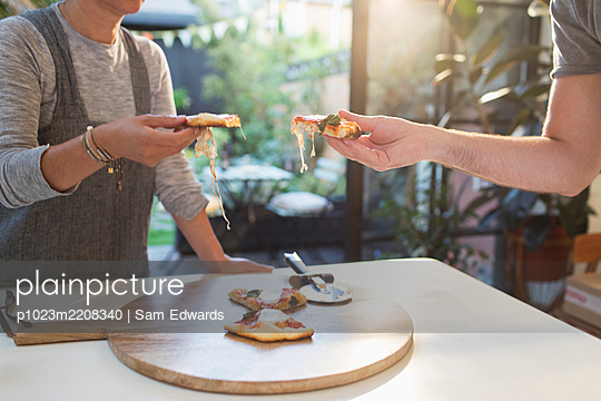 Couple enjoying homemade pizza at dining table - p1023m2208340 by Sam Edwards