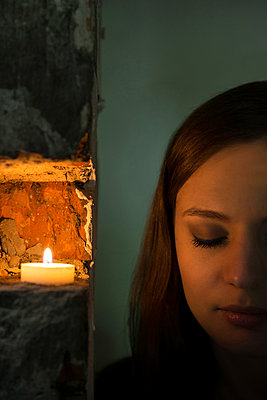 Young woman alongside tea candle - p335m1041652 by Andreas Körner