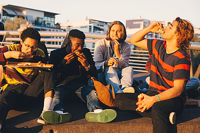 Young and teenage male friends eating pizza at harbor in city - p426m2217872 by Maskot