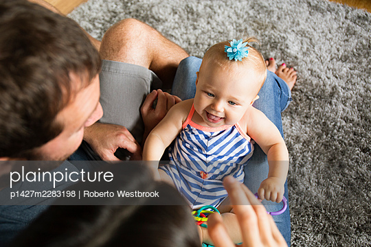 High angle view of mid adult couple playing with baby daughter on lap - p1427m2283198 by Roberto Westbrook
