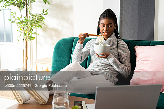 Young woman eating noodles while watching movie on laptop sitting in living room at home - p300m2225747 by Giorgio Fochesato