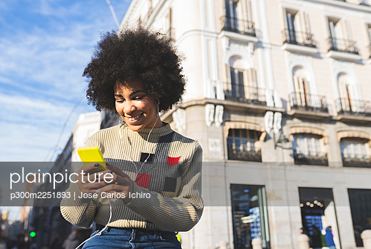 Smiling afro woman using smart phone while standing in city - p300m2251893 by Jose Carlos Ichiro