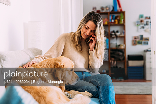 Italy, Young woman with dog at home - p924m2283034 by Eugenio Marongiu