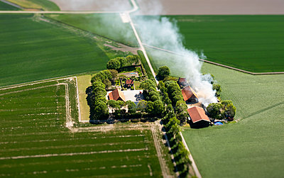 Smoke over farmstead, aerial view - p1132m2185393 by Mischa Keijser