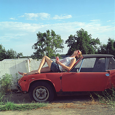 a woman lying on the hood of a red old abandonned car - p1610m2186029 by myriam tirler