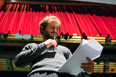 Portrait of pensive man standing on stage of theatre looking at script - p300m2103235 von Francesco Buttitta