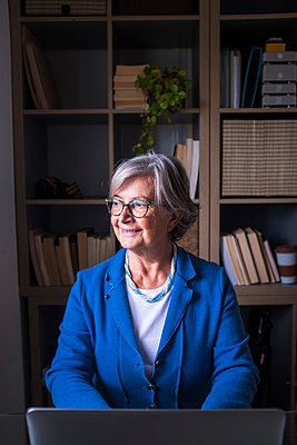 Smiling businesswoman looking away while sitting against bookshelf at home - p300m2276622 by Simona Pilolla