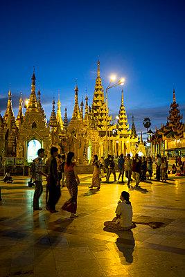 Visitors pray at Shwedagon Pagoda at dusk in Yangon, Myanmar, Southeast Asia - p934m1071300 by Linh Pham photography