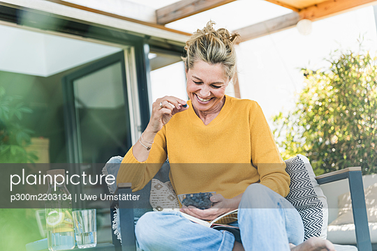 Portrait of laughing mature woman sitting on terrace eating blueberries - p300m2203134 by Uwe Umstätter