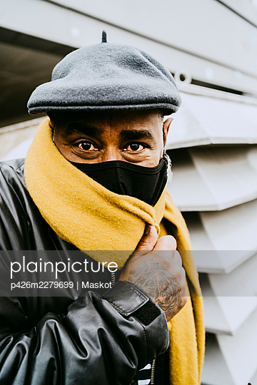 Playful senior man wearing protective mask while covering face with yellow scarf during COVID-19 - p426m2279699 by Maskot