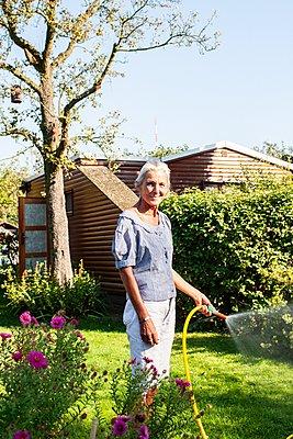 Rentnerin in ihrem Garten - p1093m2192926 von Sven Hagolani