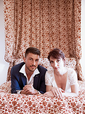 Brautpaar auf dem Bett - p1105m2126409 von Virginie Plauchut