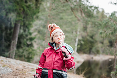young girl eating marshmallows whilst camping in a forest in Sweden - p1166m2179471 by Cavan Images
