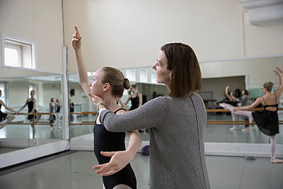 Female instructor adjusting chin of teenager ballet dancer practicing in dance studio - p1192m1403479 by Hero Images