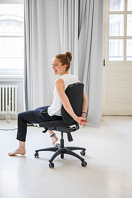 Women is spinning on an office chair - p276m2110718 by plainpicture