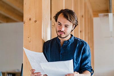 Businessman reading document in wooden open-plan office - p300m2170065 by Daniel Ingold