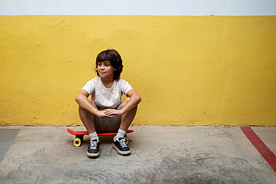 Thoughtful boy sitting on skateboard against wall - p300m2203150 by Valentina Barreto