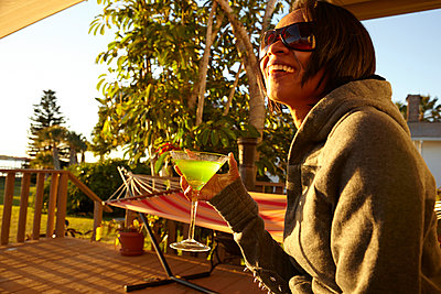 Mixed race woman having cocktail on porch - p555m1454106 by Mike Tauber