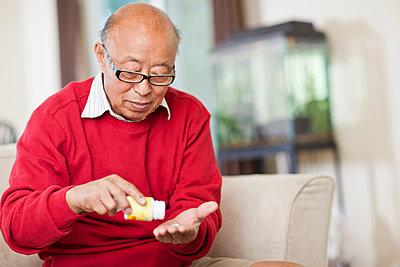 Chinese man taking medication - p555m1479786 by Take A Pix Media