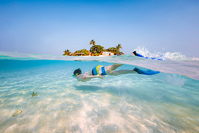 Split image over/under water of boy snorkeling underwater, Maldives (MR) - p651m2033400 by Matteo Colombo photography