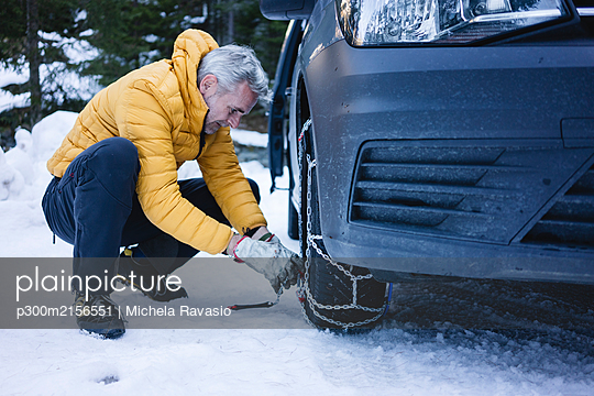 Man putting the snow chains on his car - p300m2156551 by Michela Ravasio