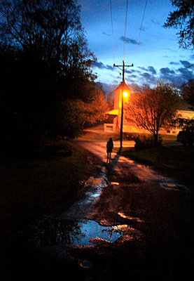 Girl walking down wet road at twilight - p1072m857312f by Michelle Kelly