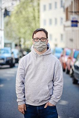 Mann mit Mundschutz auf der Straße - p1164m2177965 von Uwe Schinkel