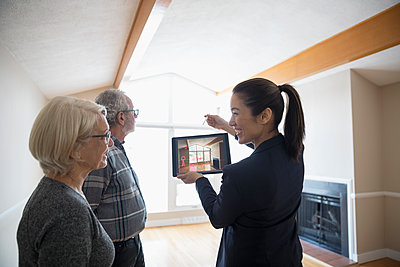 Interior designer with digital tablet showing senior couple augmented reality, planning living room remodel - p1192m1559992 by Hero Images