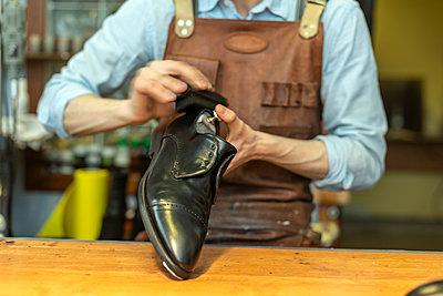 Male cobbler holding shoe while polishing at workshop - p300m2282559 by Vladimir Godnik