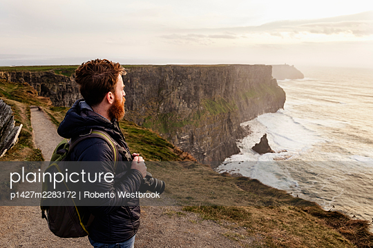 Mid adult man on The Cliffs of Moher with camera, The Burren, County Clare, Ireland - p1427m2283172 by Roberto Westbrook