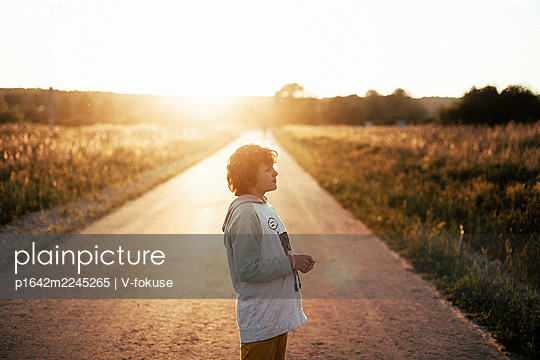 Girl standing on a road at sunset - p1642m2245265 by V-fokuse