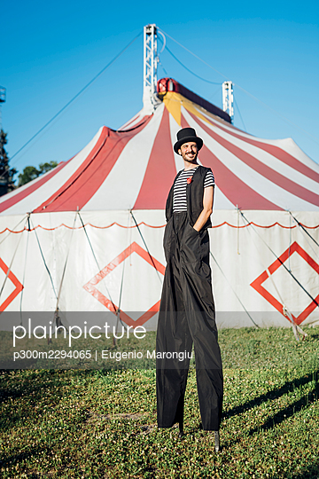 Smiling male artist standing with stilts on meadow - p300m2294065 by Eugenio Marongiu